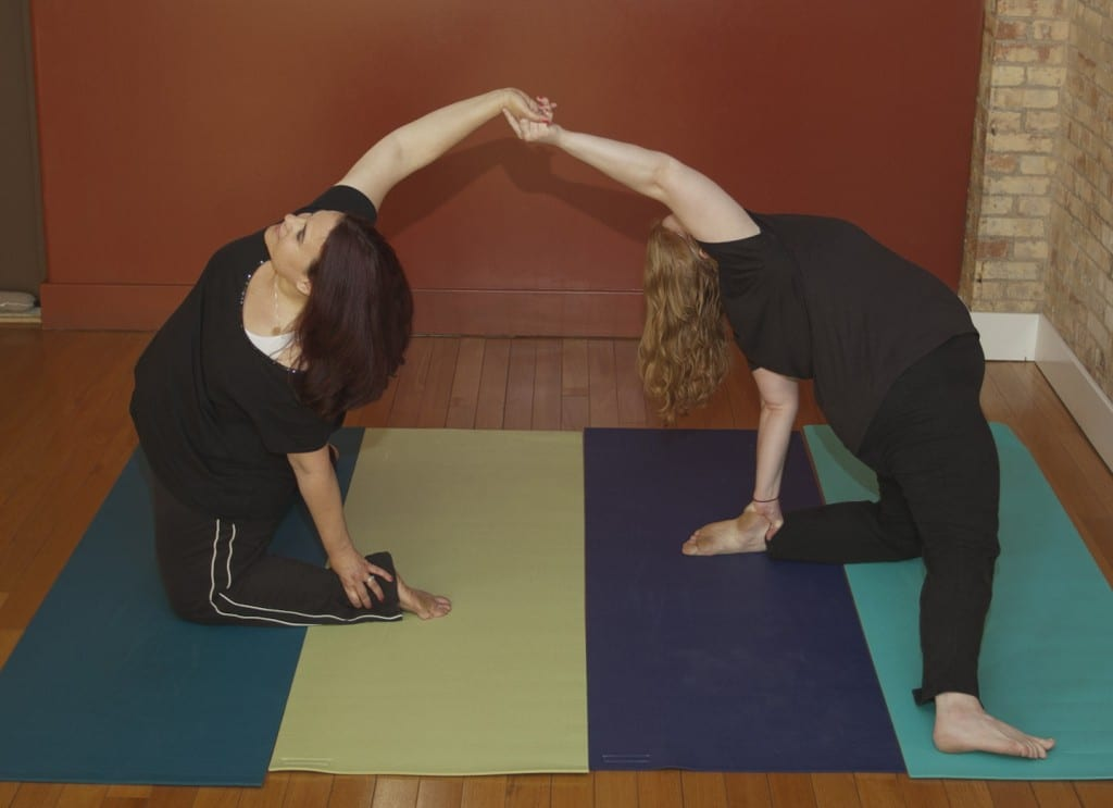 Courtney Stocker with Katie Cook doing gate pose (parighasana)