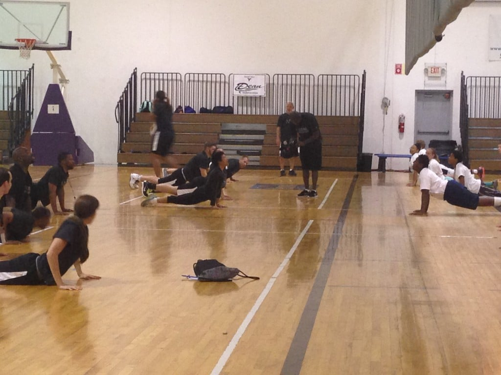 Players doing sun salutations at the Mateen Cleaves 1 Goal 1 Passion Basketball Camp in Lansing.