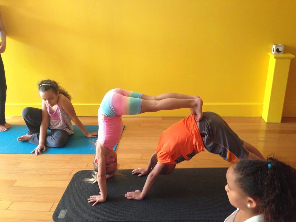 Layla in the pink and blue, upside down with Malik in downdog.